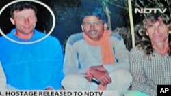 In this television shot of an undated photograph broadcast on Indian news channel NDTV on March 25, 2012, Italian national Claudio Colangelo (L) is seen pictured with fellow Italian national Paolo Bosusco (R), who continues to be held hostage by his capt