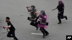Polisi anti huru-hara mengejar seorang demonstran anti-pemerintah dalam aksi protes di Bangkok, Thailand, Rabu (11/8).