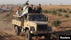 Các chiến binh thuộc Quân đội Syria Tự do cầm cờ của phe đối lập đi trên chiếc xe vận tải mà họ nói đã chiếm được từ lực lượng của chính phủ