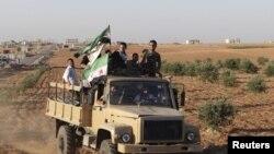 自由叙利亚军战士2012年10月15日手持反对派旗帜搭乘挂着反对派旗帜的卡车