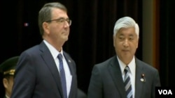 美國國防部長卡特(左)訪問日本期間和忍耐國防官員會面。(視頻截圖)