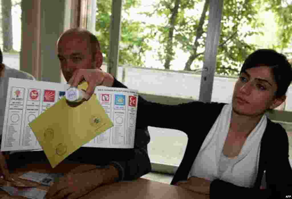 A polling station official hands over a ballot paper and a stamp at a polling station in Ankara, Turkey, June 12, 2011