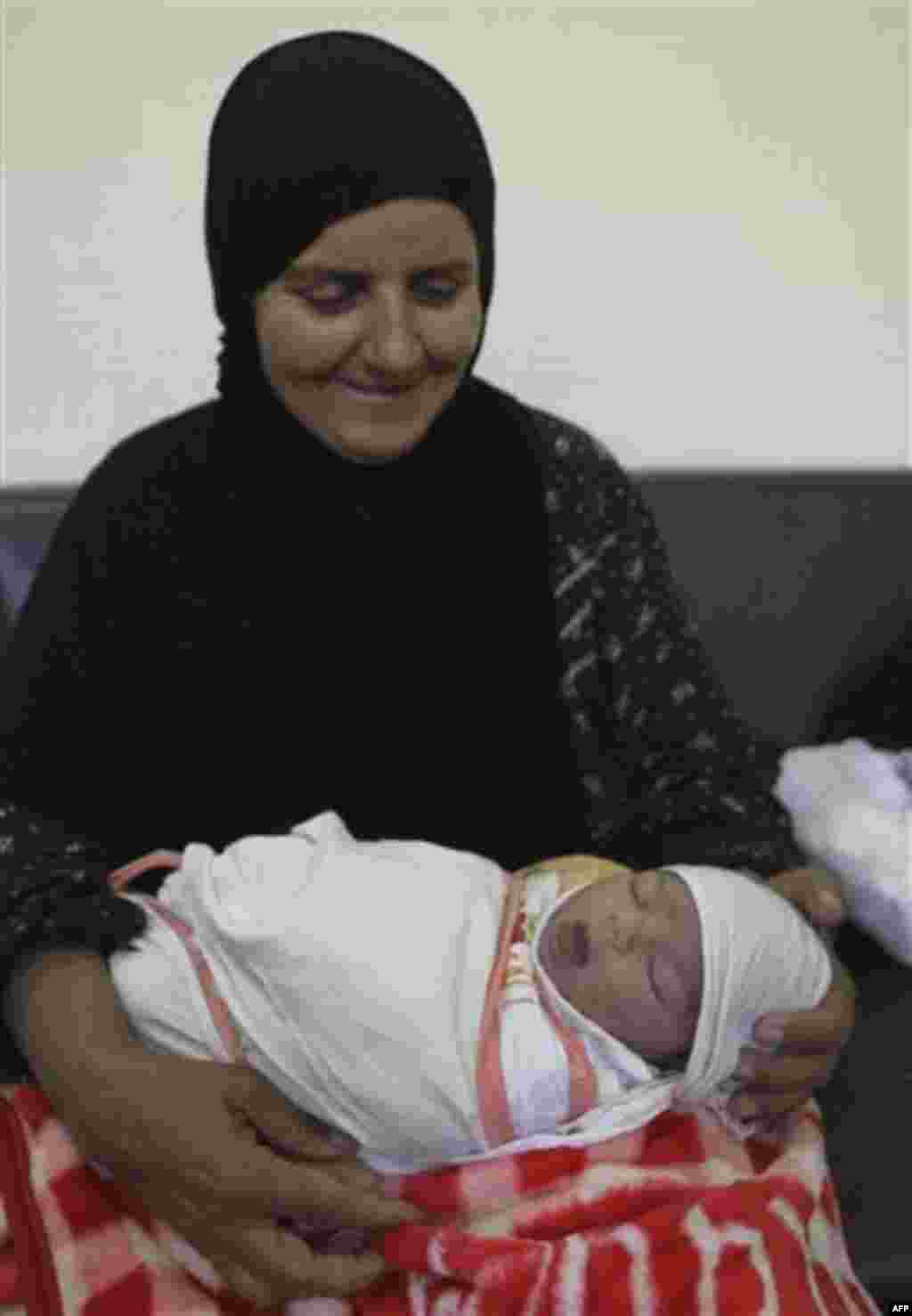 Umm Ahmed holds her granddaughter, Zahra Ahmer, born only an hour before, at a maternity hospital sponsored by the Iraqi Red Crescent Society in Baghdad, Iraq, Sunday, Oct. 30, 2011. According to Iraq's Health Ministry, Iraq witnesses the birth of more th