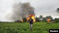 Người sắc tộc Rakhine mang theo vũ khí tự chế phía trước căn nhà đã bị đốt cháy trong vụ bạo động sắc tộc giữa người Rakhine Phật giáo và cộng đồng Hồi giáo Rohingya ở Sittwe, Miến Ðiện
