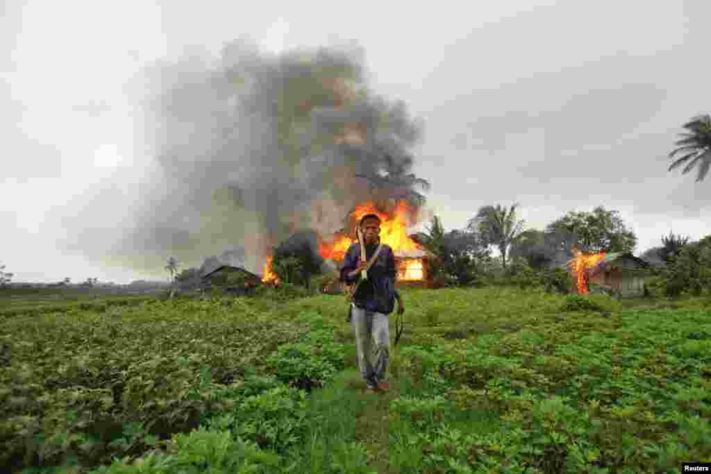 Người sắc tộc Rakhine cầm vũ khí tự chế phía trước căn nhà đã bị đốt cháy trong vụ bạo động sắc tộc giữa người Rakhine Phật giáo và cộng đồng Hồi giáo Rohingya ở Sittwe, Miến Ðiện