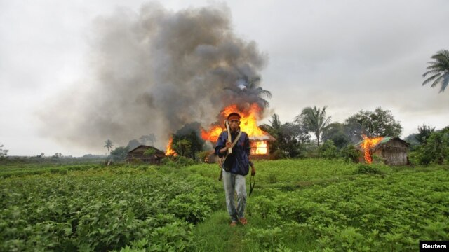 FILE - An ethnic Rakhine man holds homemade weapons as he walks in front of houses that were burnt during fighting between Buddhist Rakhine and Muslim Rohingya communities in Sittwe, June 10, 2012. Myanmar's outgoing government lifted a nearly four-year curfew in the western state of Rakhine on March 29, 2016, after communal violence.