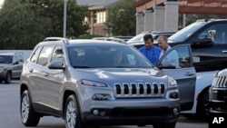 In this Nov. 5, 2015 photo, a salesperson delivers a Jeep Cherokee to a customer at a Fiat Chrysler dealership in Doral, Fla.