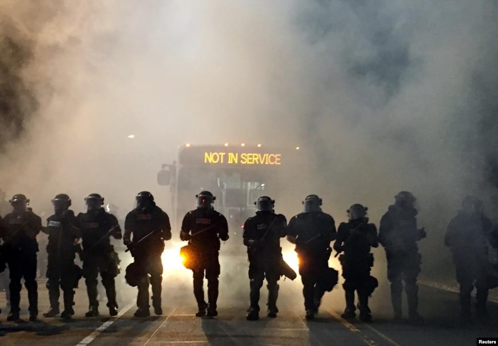 20일(현지시간) 노스캐롤라이나주 샬럿의 아파트 주차장에서 키스 러몬트 스콧이 경찰 총격에 사망한 직후 항의 시위가 격화되자, 진압장비를 갖춘 경찰 병력이 사건 현장 인근 도로를 차단한 뒤 시위대에 맞서고 있다.