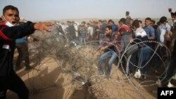 Палестинські протестувальники намагаються усунути колючий дріт з паркану на кордоні сектора Газа з Ізраїлем