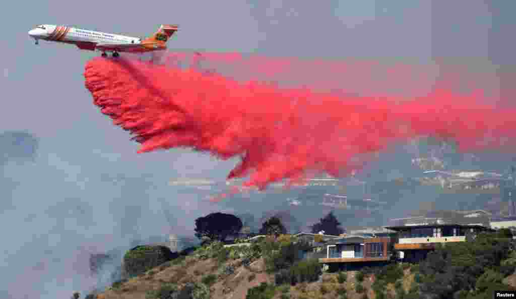 Firefighters battle a blaze from the air that was threatening homes in the Pacific Palisades community of Los Angeles, California, Oct. 21, 2019.