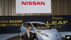 Nissan Motor Co. Chief Operating Officer Toshiyuki Shiga poses with the company's zero-emission electric car, Leaf, during a news conference at its headquarters in Yokohama, Japan, Dec. 3, 2010.