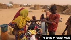 Des enfants autour de la pompe à eau dans le camp de réfugiés d'Assaga, Diffa, Niger, le 17 avril 2017 (VOA/Nicolas Pinault)