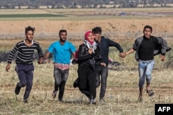 FILE - Palestinian protesters hold hands to protect a girl from shots as they run for cover during clashes with Israeli security forces following a demonstration near the border with Israel, east of Khan Yunis, in the southern Gaza Strip on March 31, 2018.