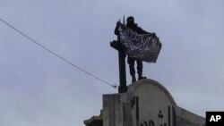 Gambar yang dipasang di akun Twitter Front al-Nusra menunjukkan seorang pejuang kelompok afiliasi al-Qaida itu mengibarkan bendera di provinsi Idlib (28/3).
