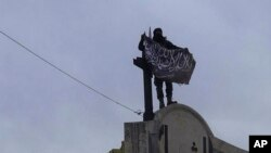 In this image posted on the Twitter page of Syria's al-Qaida-linked Nusra Front on Saturday, March 28, 2015, which is consistent with AP reporting, a fighter from Syria's al-Qaida-linked Nusra Front holds his group flag in Idlib province, north Syria.