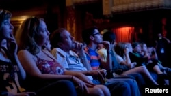 "Audience members watch ""Big Easy,"" a film at the Paramount Theater during the South by Southwest festival, Austin, Texas, March, 17, 2012."
