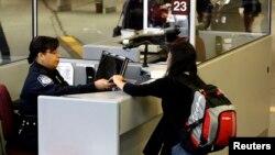 یک جوان، پاسپورت و ویزای خود را به مامور مرزی آمریکا نشان می دهد