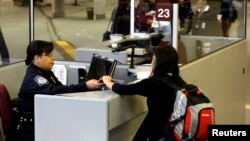 FILE - A foreign airline passenger hands travel documents to a Customs and Border Protection Officer at Hartsfield-Jackson International Airport in Atlanta, Georgia, Jan. 5, 2004.