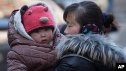 지난해 3월 중국 베이징에서 한 여성이 자녀를 안고 있다.