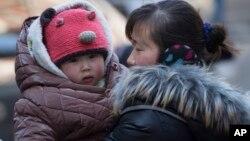 Une Chinoise avec son enfant à Pékin, en Chine, le 6 mars 2014. (AP Photo/Vincent Thian)