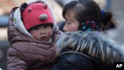 FILE - A Chinese woman cuddles her child in Beijing. China announced Thursday it was ending its long-standing one-child policy and will now allow all couples to have two children. (2014 AP PHOTO)