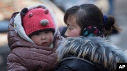 FILE - A Chinese woman cuddles her child in Beijing, China. China announced it was ending its long-standing one-child policy and will now allow all couples to have two children.