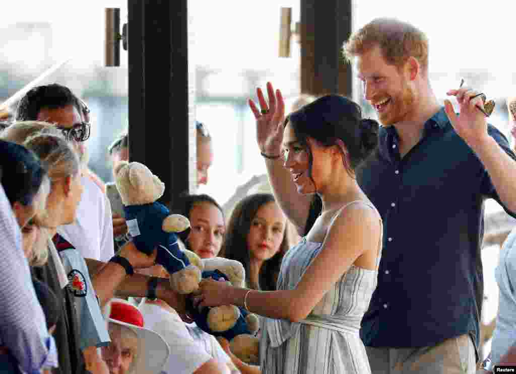 Britain's Prince Harry and Meghan, Duchess of Sussex, receive teddy bears as they meet with members of the public in Kingfisher Bay on Fraser Island in Queensland, Australia.