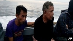 Malaysian hostages Tayudin Anjut (left) and Abdurahim Bin Sumas were rescued in Sulu province, southern Philippines, March 23, 2017. The two Malaysian sailors had been held captive for eight months by Muslim militants. On Saturday, a cargo ship's captain was rescued.