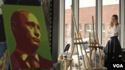 An activist is seen talking on her phone at the office of pro-Kremlin youth group SET (Network). To her left is a portrait of Russian President Vladimir Putin. (VOA video screengrab)