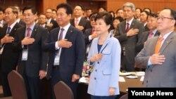 박근혜 한국 대통령이 13일 청와대에서 열린 민주평통 해외자문위원과의 통일대화에서 참석자들과 함께 국기에 대한 경례를 하고 있다.