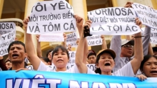 """FILE - Vietnamese protesters hold banners reading """"Formosa destroys the environment, which is a crime"""" and """"I love the sea, shrimp and fish"""" during a rally denouncing recent mass fish deaths in Vietnam's central province, in Hanoi, Vietnam, May 1, 2016."""