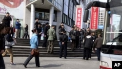 FILE - Plainclothes security personnel film as they gather to load detained worshippers onto a waiting bus near a building that leaders of the unregistered Shouwang house church had told parishioners to gather in Beijing, China, April 10, 2011.