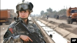 FILE - U.S. soldier Pfc. Janelle Zalkovsky, from civil affairs unit of 1st Battalion, 320th Field Artillery Regiment, 101st Airborne Division, provides security while other soldiers survey a newly constructed road in Ibriam Jaffes, Iraq.