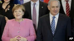 German Chancellor Angela Merkel, left, and the Prime Minister of Israel Benjamin Netanyahu, right, pose with government members for a group photo during a one day German-Israeli governmental meeting at the chancellery in Berlin, Germany, Feb. 16, 2016.