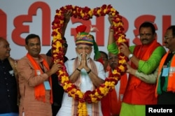 India's Prime Minister Narendra Modi is presented with a garland during an election campaign rally in Himmatnagar, Gujarat, April 17, 2019.