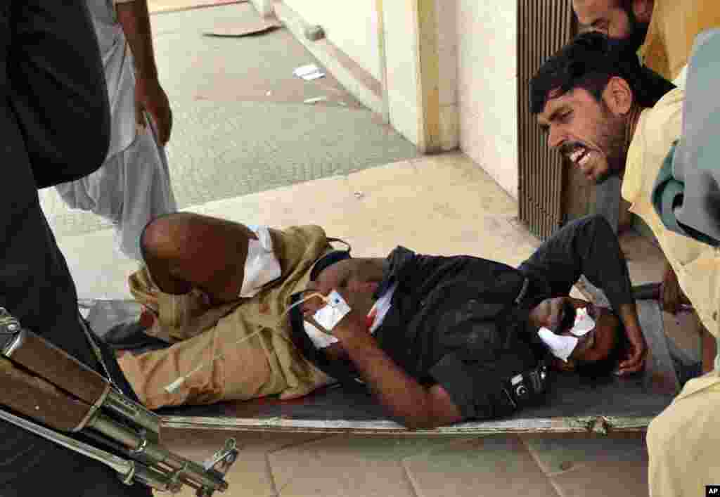 People carry a wounded police officer from the site of a bombing in Quetta, Pakistan, August 8, 2013.