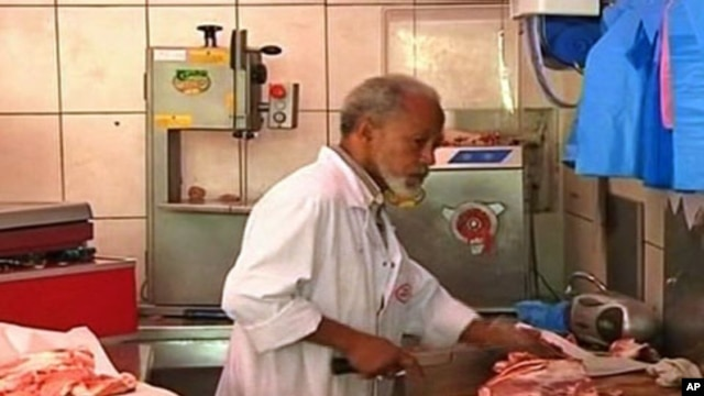Butcher Haj Mohammed chops pieces of meat at his Halal butcher shop and wraps each carefully for his customers in in Paris's Muslim quarter