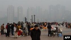 2013年2月,重庆居民在朝天门公园,背景是新建的社会保障房。薄熙来由于社会保障房等项目而在当地得人心,但也留下巨额债务