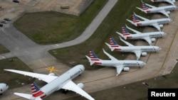 Pesawat penumpang American Airlines (kiri) diparkir karena pengurangan penerbangan yang dilakukan untuk memperlambat penyebaran Covid-19, di Bandara Internasional Tulsa di Tulsa, Oklahoma, AS, 23 Maret 2020. (Foto: Reuters)