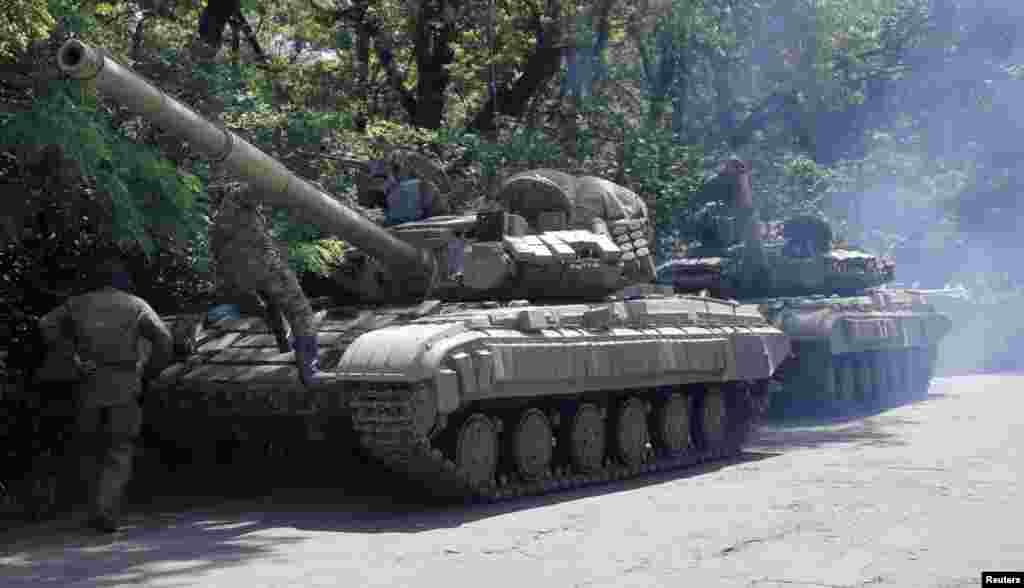 Pro-Russian troops prepare to travel in a tank on a road near the town of Yanakiyevo, Donetsk region, eastern Ukraine, June 20, 2014.