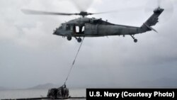 """A MH-60S helicopter, from the """"Island Knights"""" of Helicopter Sea Combat Squadron (HSC) 25, from the Military Sealift Command dry cargo and ammunition ship USNS Charles Drew (T AKE 10), transports a pallet of water en route to the Republic of the Philippin"""