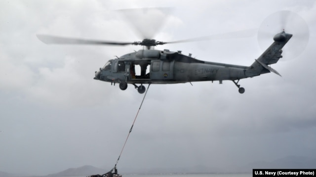"A MH-60S helicopter, from the ""Island Knights"" of Helicopter Sea Combat Squadron (HSC) 25, from the Military Sealift Command dry cargo and ammunition ship USNS Charles Drew (T AKE 10), transports a pallet of water en route to the Republic of the Philippines, Nov. 14, 2013."