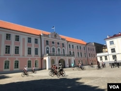 Bicyclists are seen in front of the Estonian Parliament building, Tallinn, Estonia, July 15, 2018. (S. Herman/VOA)