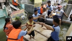 Rescuers move children to an evacuation center at Malabon city, north of Manila, Philippines, Aug. 1, 2012.