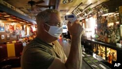 Cheers to You bar owner Bob Brown tests a thermometer at his bar Friday, May 1, 2020, in Salt Lake City. Brown realize he needs to hire two or three new people just to enforce social distancing guidelines. (AP Photo/Rick Bowmer)