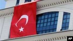 A Turkish flag is hung from the headquarters of Turkish Prime Minister Recep Tayyip Erdogan's ruling party, apparently to conceal the damage after assailants fired a rocket on the building, in Ankara, March 20, 2013.