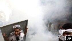埃及警方11月23 日在解放廣場附近發放催淚瓦斯,一名示威者以金屬牌作防護