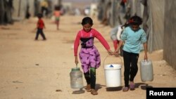 Internally displaced Syrian girls carry water containers in Jrzinaz camp in the southern part of Idlib, Syria, June 21, 2016.