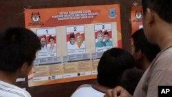 Para pemilih memperhatikan foto-foto kandidat pilkada di sebuah TPS di Tangerang, 9 Desember 2015. (Foto: AP)