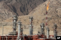 FILE - A gas flare burns in a gas refinery in South Pars gas field, on the northern coast of the Persian Gulf, in Asalouyeh, Iran, Jan. 22, 2014.